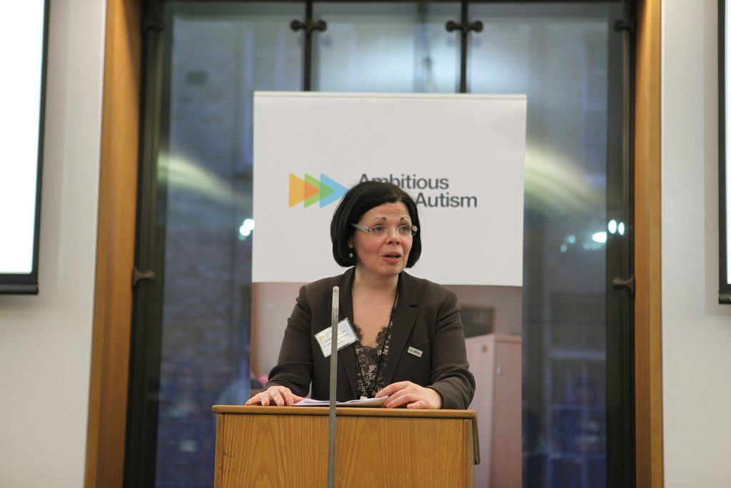 A woman talking at an event surrounding autism